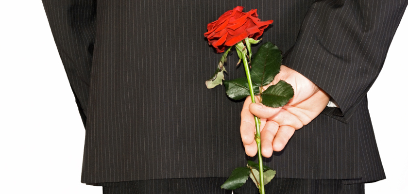 sales man hiding back red rose